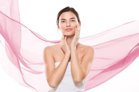 Belle jeune femme regardant la caméra isolée sur fond blanc avec des vagues de tissu rose. Beauté satisfaite fille toucher son visage et en regardant la caméra. Soins de la peau et le concept spa beauté. Banque d'images - 65157949