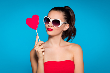 Portrait of beautiful woman with heart shaped lolly isolated on blue background. Portrait of beautiful brunette girl with red lollypop looking at camera. Funny woman in red dress and white sunglasses.