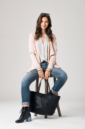 Portrait of young brunette woman sitting on wooden stool and looking at camera. Smiling fashion girl wearing stylish clothes. Happy beautiful woman with sunglasses and shopping bag sitting on stool. Stock Photo