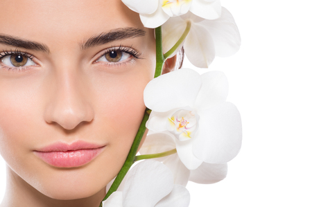 Close up face of beautiful young woman with white orchid flower on her cheek. Portrait of a brunette girl with perfect skin face with orchid isolated on white background with copy space. Young woman with pure skin and flower on face looking at camera.