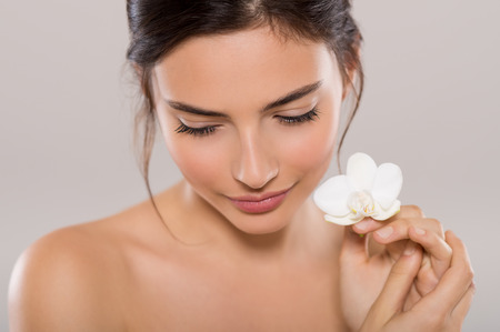 Beautiful young woman holding one orchid flower near face while looking down. Close up face of brunette woman with healthy skin and white flowers near face isolated on grey background. Beauty and body care concept. Stock fotó