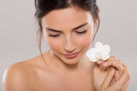 Mooie jonge vrouw met een orchidee bloem in de buurt gezicht, terwijl naar beneden te kijken. Close-up gezicht van brunette vrouw met een gezonde huid en witte bloemen in de buurt van gezicht geïsoleerd op een grijze achtergrond. Beauty en lichaamsverzorging concept.