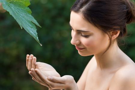 Joven y bella mujer tomar una gota de agua clara de una hoja en la naturaleza. belleza natural refrescarse con agua directamente de una hoja de parra. Símbolo de la pureza, el cuidado del cuerpo y la armonía de la naturaleza.