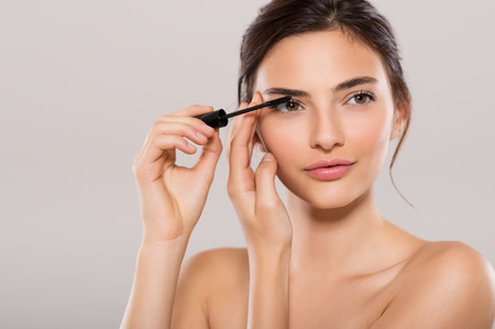 Woman applying black mascara on eyelashes with makeup brush. Young beautiful woman applying mascara makeup on eyes by brush. Portrait of brunette beauty girl applying makeup over grey background.