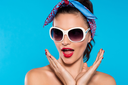 Young excited woman wearing sunglasses and red bandana screaming. Surprised brunette girl over blue background. Pin up girl announcing something with happy and shocked expression.