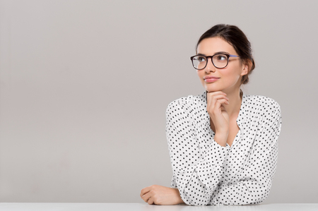 girl glasses: Beautiful young businesswoman wearing glasses and thinking with hand on chin. Smiling pensive woman with eyeglasses looking away isolated on grey background. Fashion and contemplative girl smiling and meditating on project. Stock Photo