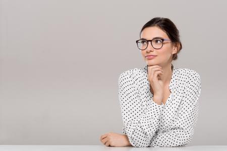 Piękna młoda businesswoman noszenie okularów i myśli z ręką na brodzie. Uśmiechnięta kobieta Frasobliwy z okularów odwracając samodzielnie na szarym tle. Moda i kontemplacyjne Dziewczynka uśmiecha się i medytując nad projektem.