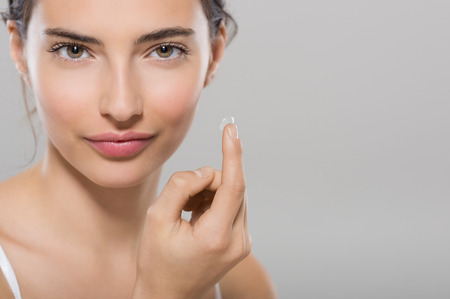 Young woman holding contact lens on index finger with copy space. Close up face of healthy beautiful woman about to wear contact lens. Eyesight and ophthalmology concept. Stock Photo
