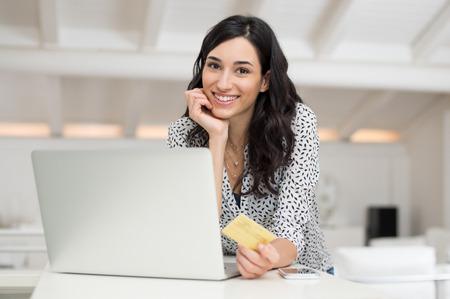 Joven feliz haciendo compras en línea con su portátil en casa. Retrato de la mujer sonriente en la tarjeta de celebración de crédito casual y mirando a la cámara. La muchacha hermosa el pago de facturas en línea utilizando tarjeta de oro.