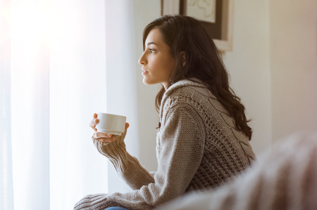 Young woman looking over window pane holding coffee. Thoughtful woman thinking and looking away while drinking hot tea. Woman in warm sweater looking outside window while drinking tea at morning. Stock Photo
