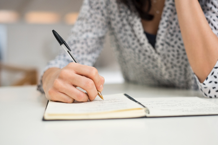 Close up hand of a young woman writing in diary on white table. Girl hand with pen writing on a notebook at home. Female student taking notesb and studying at her desk.