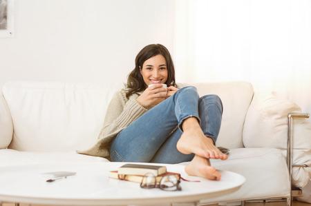 Felice donna seduta sul divano con una tazza di tè in salotto. Ritratto di una giovane donna di bere una tazza di caffè mentre ci si rilassa sul divano di casa. Ragazza sorridente con il caffè caldo giacca di lana bere e guardando a porte chiuse. Archivio Fotografico - 68789612