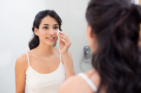 Healthy fresh girl removing make up from her face with cotton pad. Smiling girl cleaning her face in bathroom. Beautiful healthy woman making scrub on her face. Stock Photo