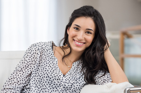 Closeup of a smiling young woman looking at camera. Portrait of happy brunette girl smiling at home. Relaxed woman at home smiling. Foto de archivo