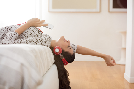Happy young woman with headphones listening to music while lying on bed at home. Beautiful brunette girl with headphones relaxing on the bed. Smiling woman enjoying music on headphones holding phone and stretching out arms in bedroom.   Фото со стока