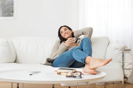 Jonge glimlachende vrouw zittend op de bank en kijken, terwijl het drinken van hete thee. Jonge brunette vrouw denken thuis in de vrije tijd. Het gelukkige meisje ontspannen thuis op een heldere winterse ochtend.