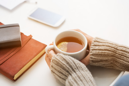 on the handphone: Close up of woman hands holding a cup of lemon tea on white table in a winter afternoon. Woman hands holding hot drink on table. Female hands with beige warm sweater holding hot tea with a slice of lemon.  Stock Photo