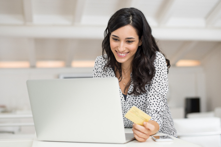 paying: Happy young woman holding a credit card and shopping online at home. Beautiful girl using laptop to shop online with creditcard. Smiling woman using laptop and credit card for online payment. Stock Photo