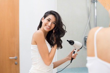 Beautiful girl using a hair dryer and smiling while looking at the mirror. Smiling woman drying hair with hair dry machine. Happy girl looking at mirror while using hair dryer in the bathroom.