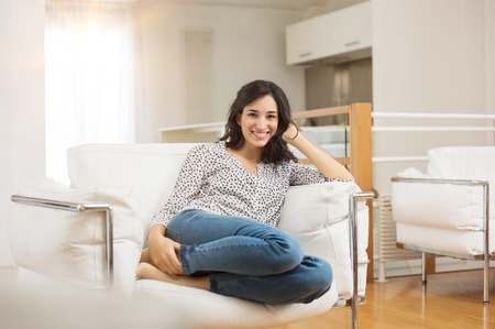 Happy young woman sitting on sofa at home and looking at camera. Portrait of comfortable young woman in casual relaxing on armchair. Portrait of beautiful brunette woman smiling while sitting on couch at home.