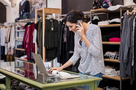 Junge Unternehmerin über Telefon zu sprechen, während mit Laptop-Store in ihrer Kleidung zu überprüfen. Junge Unternehmer in lässig mit Laptop und sprechen auf Handy. Filialleiter Frau wichtige Dokumente auf dem Laptop zu überprüfen. Small Business-Konzept. Standard-Bild
