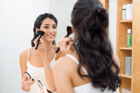 Beautiful young woman doing make up in her bathroom. Happy young woman applying blush on cheek in front of a mirror in bathroom. Brunette girl applying foundation on face with brush.