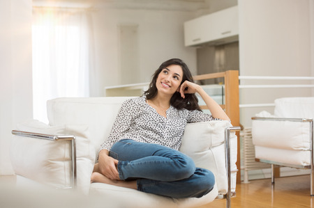 Young dreaming woman sitting on sofa at home. Thoughtful young woman sitting in living room and looking up. Smiling woman relaxing on couch in a modern home. Zdjęcie Seryjne - 71465177