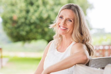 Happy blonde mature woman sitting outdoor and thinking. Senior woman relaxing on a wooden bench under the tree in a summer day. Portrait of middle aged woman smiling and daydreaming. 写真素材