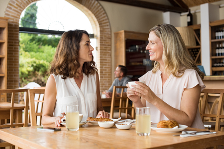 Two beautiful mature women holding cup of coffee and talking to each other in a cafeteria. Senior women in conversation while having breakfast. Happy middle aged friends meeting up for coffee.