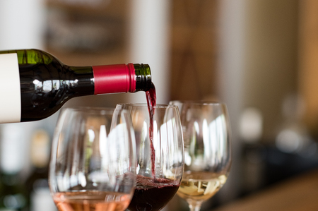 Pouring red wine from bottle into the wineglass on bar. Close up of red wine pouring from bottle to glass in a winery. Wine tasting in a winehouse. 스톡 콘텐츠