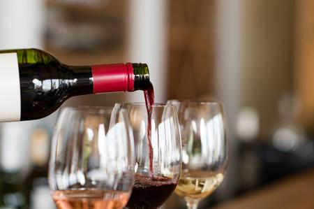 Giet rode wijn van de fles in de wijnglas op de bar. Close-up van rode wijn gieten van fles naar glas in een wijnmakerij. Wijnproeverij in een wijnhuis. Stockfoto