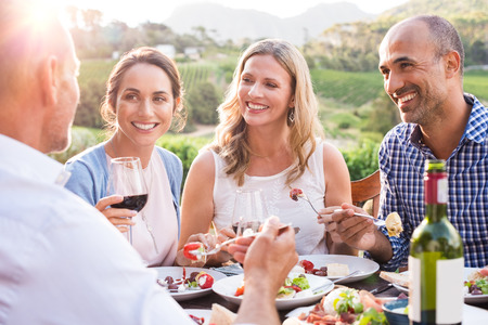 Group of mature people eating together in a vineyard in a summer day. Happy woman sipping wine while talking to friends during a lunch in a winery. Happy senior couple having dinner with wine at sunset.