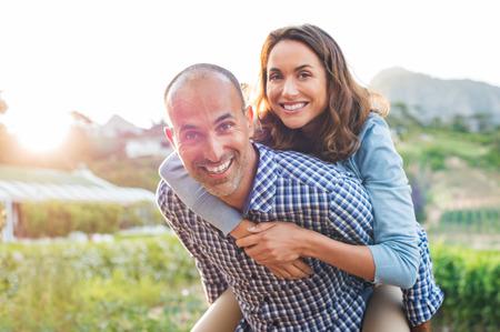 日没時にアウトドアを楽しんで幸せな成熟したカップル。カメラを見ながら彼女の男におんぶに笑顔の女性。彼の妻の肩に運ぶ中年の男の肖像画。