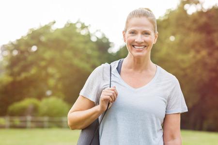 運動の準備灰色のヨガマットを持って先輩の美しい女性。公園でフィットネス マットと成熟した笑顔の女性の肖像画。屋外に立っているヨガの服に