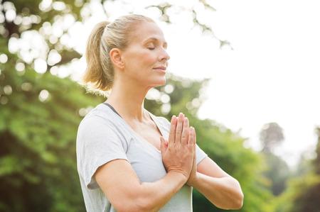De rijpe vrouw in park toetredende handen met gesloten ogen en mediteert. De ontspannen hogere vrouw met aangesloten handen ademt diep met gesloten ogen. Gezonde vrouw die openlucht mediteert. Stockfoto