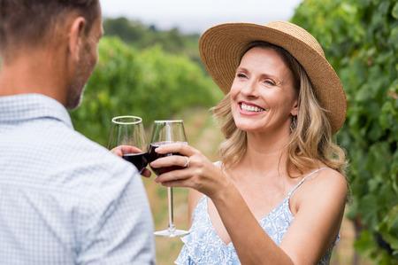 Paar wijnbouwers die wijn in wijngaard drinken. Close-up gezicht van gelukkige lachende vrouw met strohoed roosteren met haar man. Ouder stel proeverij wijn in wijngaard. Stockfoto