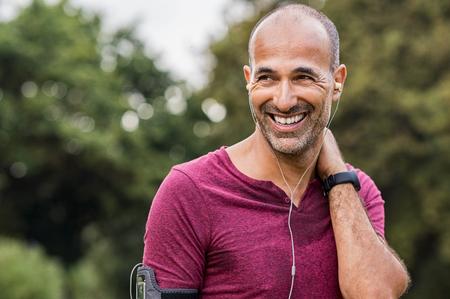 成熟した男はジョギングの後休憩中に音楽を聴きます。幸せなハゲの年配の男性は運動後にリフレッシュ感します。フィットネス後の音楽を聴きな