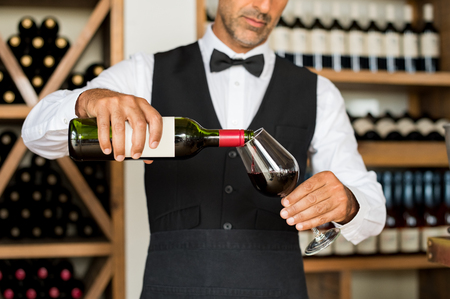 Close up of sommelier hands pouring red wine in a glass. Mature man in waistcoat pouring red wine in glass. Bartender serving wine in glass with shelfs of bottles behind. Zdjęcie Seryjne