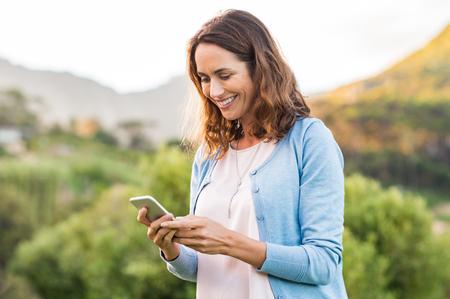 Madura mujer feliz utilizando teléfono celular en el parque. Mujer sonriente mensaje de lectura en el teléfono inteligente. Brunette latino mujer escribiendo un mensaje en su teléfono después de recibir un correo electrónico. Foto de archivo