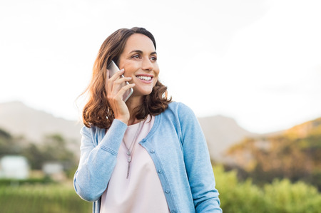communication: Mature happy woman talking on phone outdoor during sunset. Cheerful hispnic woman using smartphone and looking away. Happy woman in conversation using mobile phone and smiling.