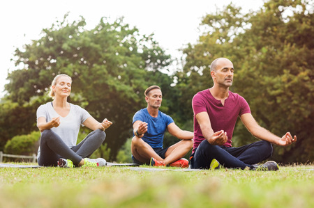 Group of middle aged people doing yoga sitting on grass. Three people practicing meditation and yoga at park on a bright morning. Mature woman and two mid men meditating together in a lotus position. Banque d'images
