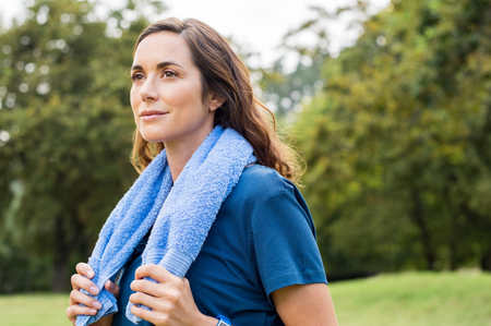 resting: Beautiful fit mature woman resting after workout. Proud brunette woman relaxing with blue towel around neck after yoga in park. Thoughtful mid adult woman thinking after sport and looking away. Stock Photo