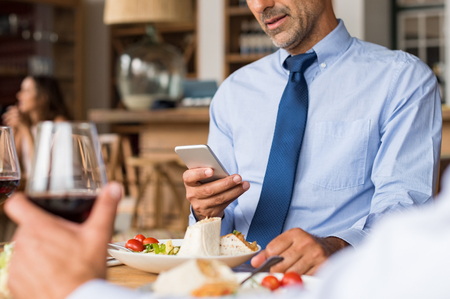 communication: Hands of a businessman using phone at restaurant during business lunch. Closeup of a man hand reading email on phone while having lunch in cafe. Businessman sending message and updating team after a meeting.