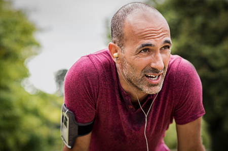 Portrait of athletic mature man after run. Handsome senior man resting after jog at the park on a sunny day. Sweaty multiethnic man listening to music while jogging. Stockfoto