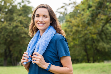運動後公園で笑っている幸せな成熟した女。カメラ目線の首の周りの青いタオルで中年の女性の肖像画。ヨガや屋外運動後エネルギッシュな感じて