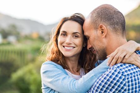 Ouder romantisch paar omarmt buiten. Gelukkige vrouw omhelzen haar multietnische vriendje bij het park tijdens zonsondergang. Lachende brunette vrouw verliefd op haar man kijken naar camera.