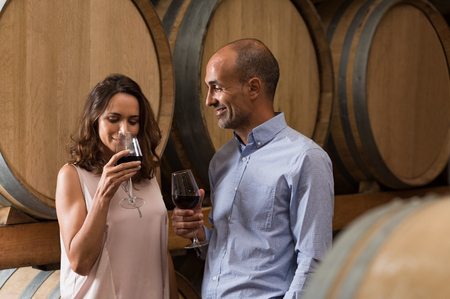 Mature couple tasting a glass of red wine in a traditional cellar surrounded by wooden barrels. Happy mature woman smelling a glass of red wine. Loving couple tasting wines in winery cellar. Stock Photo