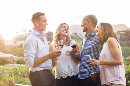 wineries: Two relaxed mature couples laughing and enjoy glasses of red wine at sunset. Group of happy friends celebrating outdoor and toasting with glassess. Happy man and smiling women having fun at vineyard.