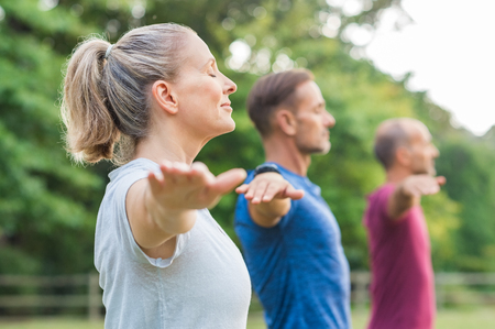 Groep senioren met gesloten ogen die armen uitrekken op het park. Gelukkige volwassen mensen doen yoga-oefening buiten op een lichte ochtend. Yoga klas met vrouw en mannen die adem uitoefenen met uitgestrekte armen.