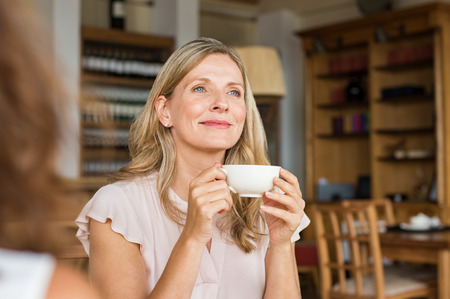 Mature woman holding coffee cup and looking away at cafeteria. Thoughtful mature woman thinking while holding coffee cup. Happy and satisfied woman enjoying cappuccino at cafe.